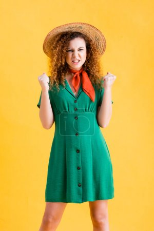 Photo for Angry woman in straw hat and green dress standing with clenched fists on yellow - Royalty Free Image