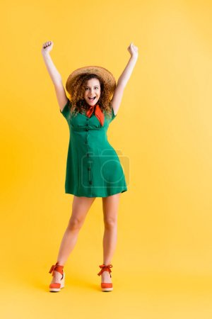 full length of amazed woman in green dress and straw hat standing with hands above head on yellow