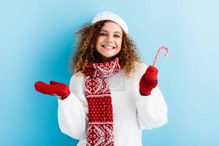 Photo pour Jeune femme gaie en mitaines rouges tenant canne à bonbons sur bleu - image libre de droit