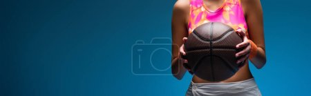 Photo for Cropped view of young woman in sportswear holding basketball on blue, banner - Royalty Free Image
