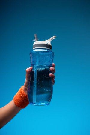 Photo for Cropped view of woman holding sports bottle on blue - Royalty Free Image