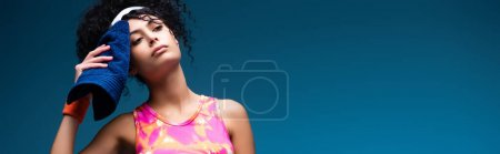 Photo for Tired sportswoman wiping sweat with towel on blue, banner - Royalty Free Image
