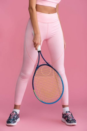 Photo for Cropped view of woman in sportswear holding tennis racket on pink - Royalty Free Image