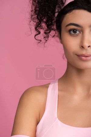 Photo for Cropped view of young and curly sportswoman in headband looking at camera isolated on pink - Royalty Free Image