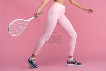 cropped view of tattooed young sportive woman in sneakers holding racket while playing tennis  on pink