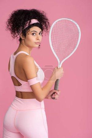 Photo pour Jeune femme en vêtements de sport tenant raquette de tennis isolé sur rose - image libre de droit