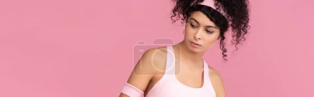 Photo for Curly woman in sportswear looking away isolated on pink, banner - Royalty Free Image