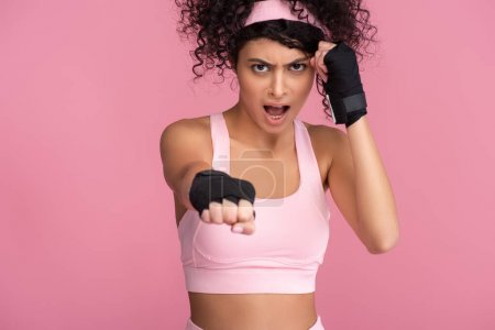 curly young woman in sportswear with bondage on hands screaming while exercising isolated on pink