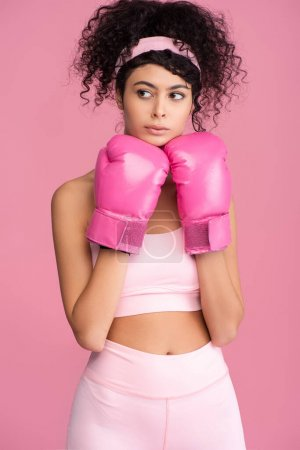 Photo for Curly young woman in sportswear and boxing gloves looking away isolated on pink - Royalty Free Image