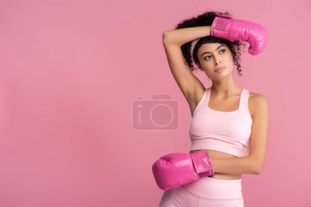 brunette and curly woman in sportswear and boxing gloves isolated on pink