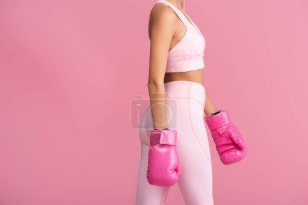 Photo pour Vue recadrée de la jeune sportive en gants de boxe isolés sur rose - image libre de droit