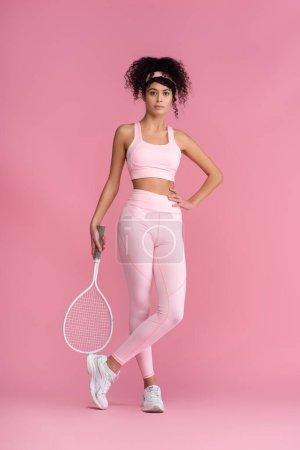 Photo pour Toute la longueur de la femme bouclée en vêtements de sport tenant raquette de tennis tout en se tenant avec la main sur la hanche et les jambes croisées sur rose - image libre de droit