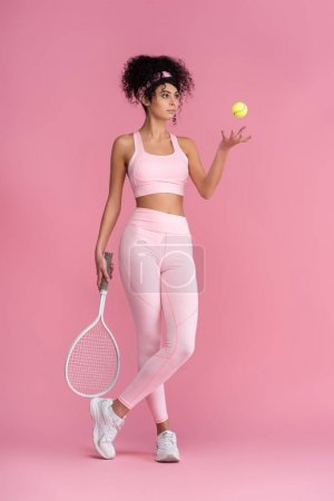 full length of curly woman in sportswear holding tennis racket while standing with crossed legs and throwing ball in air on pink