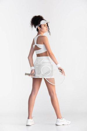 Photo pour Toute la longueur du jeune joueur bouclé en vêtements de sport tenant raquette de tennis derrière le dos et debout sur blanc - image libre de droit