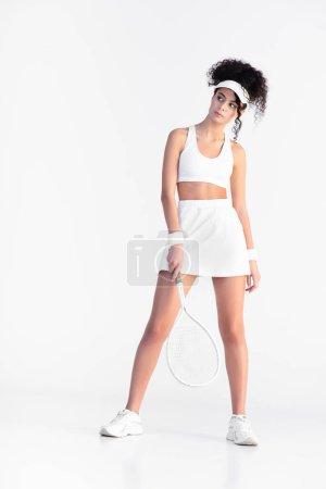Photo pour Toute la longueur de jeune joueur bouclé en vêtements de sport tenant raquette de tennis et debout sur blanc - image libre de droit