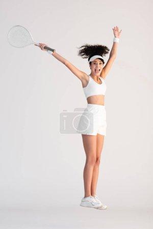 Photo pour Pleine longueur de femme excitée en vêtements de sport tenant raquette de tennis et sautant sur blanc - image libre de droit