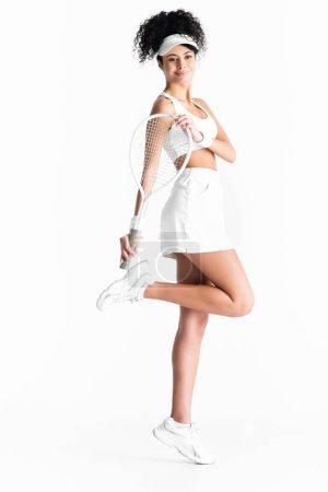Photo pour Pleine longueur de sportswoman heureux en casquette tenant raquette de tennis et posant isolé sur blanc - image libre de droit