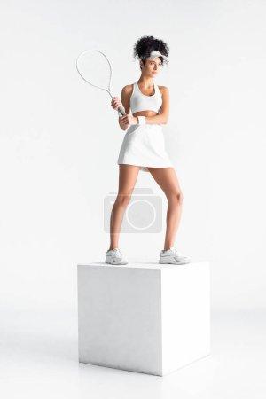 Photo pour Longueur totale de jeune sportive en bonnet tenant raquette de tennis et debout sur cube sur blanc - image libre de droit