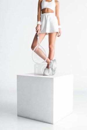 Photo pour Vue partielle de la jeune sportive tenant une raquette de tennis et debout sur cube sur blanc - image libre de droit