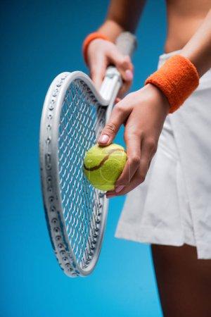 Photo pour Vue recadrée de la jeune femme sportive tenant raquette de tennis et ballon tout en jouant sur le bleu - image libre de droit