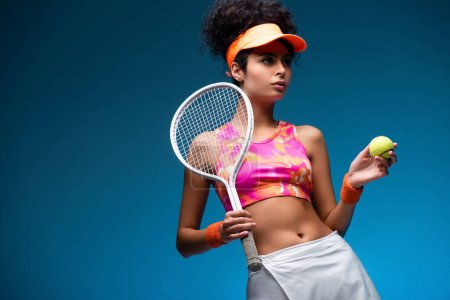 Photo for Sportive and curly woman holding tennis racket and ball on blue - Royalty Free Image