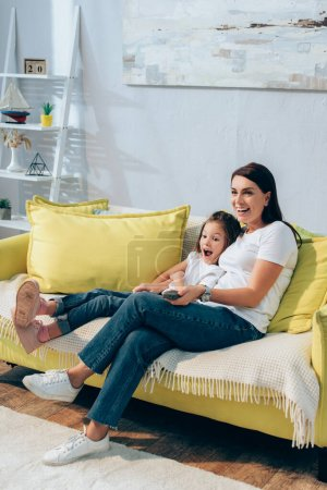 Photo for Full length of happy mother with remote controller hugging excited daughter on couch - Royalty Free Image