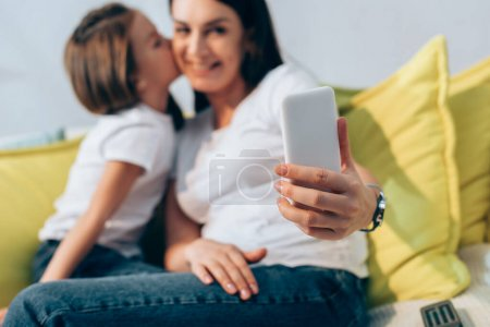 Photo for Daughter kissing smiling mother during selfie at home on blurred background - Royalty Free Image
