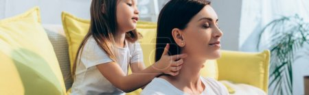Daughter plaiting hair of smiling mother with closed eyes at home on blurred background, banner