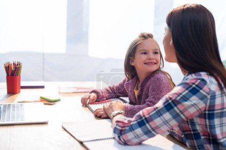 Photo pour Fille joyeuse regardant la mère au bureau avec papeterie et ordinateur portable sur fond flou - image libre de droit