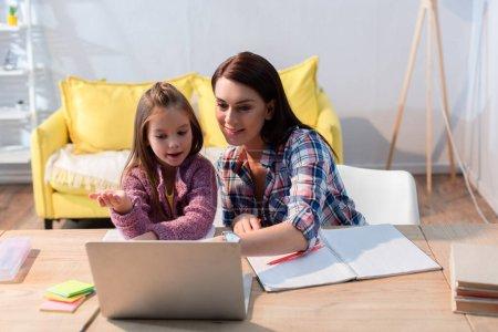 Photo pour Mère souriante regardant un ordinateur portable près de sa fille gesticulant dans le salon - image libre de droit
