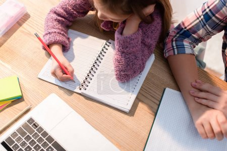 Top view of daughter writing in notebook near mother at desk with stationery and laptop
