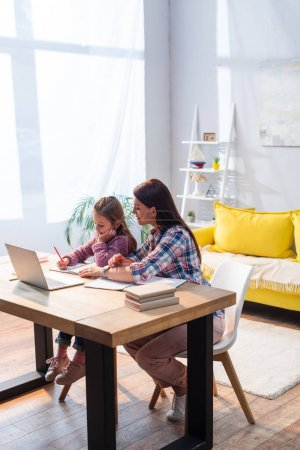 Full length of smiling mother sitting near daughter writing in notebook near laptop in living room