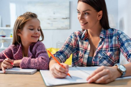 Lächelnde Mutter blickt Tochter an, während sie am Schreibtisch auf verschwommenem Hintergrund ein Buch schreibt
