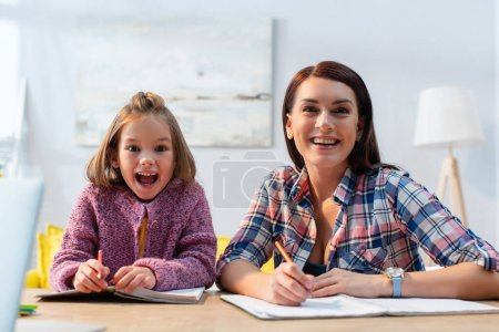 Photo for Smiling mother and excited daughter with open mouth looking at camera with blurred living room on background - Royalty Free Image