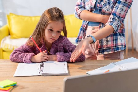 Photo for Upset daughter with pencil and notebook near mother pointing with hand near desk on blurred foreground - Royalty Free Image