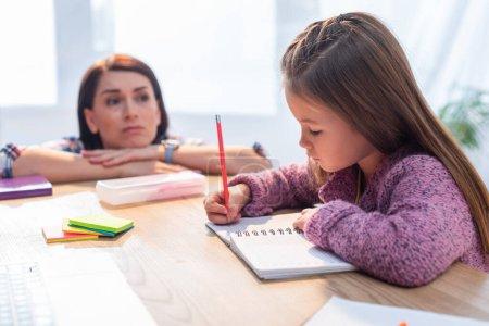 Photo pour Mère bouleversée regardant sa fille écrire dans un cahier au bureau sur un fond flou - image libre de droit