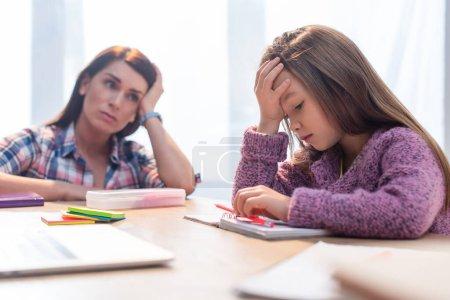 Photo pour Fille fatiguée regardant ordinateur portable sur le bureau avec mère inquiète floue sur fond - image libre de droit