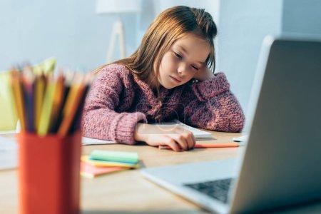 Photo pour Fille endormie au bureau avec papeterie et ordinateur portable flou au premier plan - image libre de droit