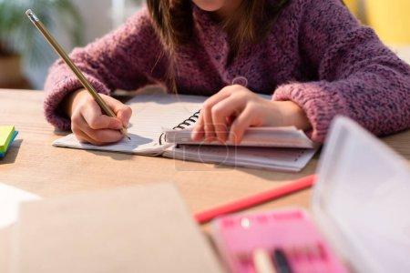 Photo pour Vue recadrée de la fille avec un crayon écrit dans un cahier au bureau sur le premier plan flou - image libre de droit