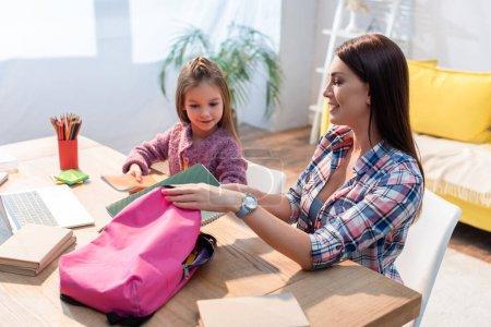 Photo pour Mère heureuse mettant le livre de copie dans le sac à dos tout en s'asseyant près de la fille au bureau sur fond flou - image libre de droit