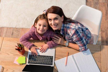 Photo pour Vue du dessus de la mère et de la fille souriantes regardant la caméra alors qu'elles étaient assises au bureau avec un ordinateur portable et de la papeterie - image libre de droit