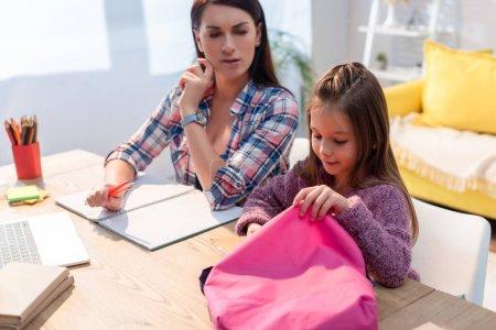 Photo pour Fille positive avec sac à dos assis près de la mère sérieuse au bureau sur fond flou - image libre de droit