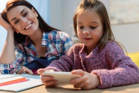 Photo pour Fille positive tenant smartphone près de la mère à la maison sur le premier plan flou - image libre de droit