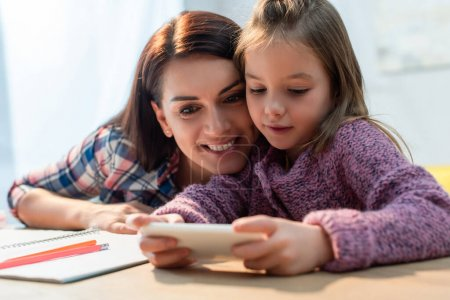 Photo for Happy mother and daughter with smartphone taking selfie at desk on blurred foreground - Royalty Free Image