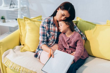 Upset mother with pencil and copy book hugging daughter sleeping on couch