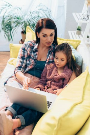 Photo for Mother talking and looking at laptop while hugging daughter on couch on blurred background - Royalty Free Image