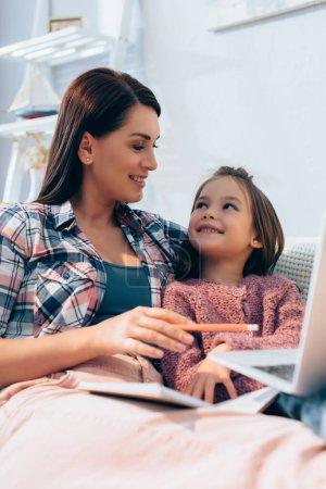 Photo pour Mère souriante regardant sa fille tout en pointant le crayon vers un ordinateur portable flou au premier plan - image libre de droit
