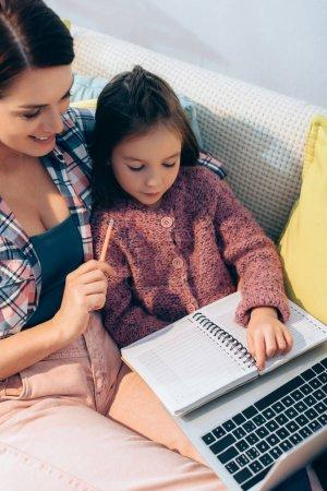 Photo pour Mère et fille souriantes regardant le carnet près de l'ordinateur portable sur le canapé - image libre de droit
