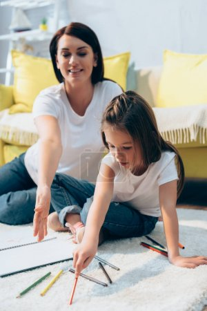 Photo for Daughter with colored pencil sitting near smiling mother on floor on blurred background - Royalty Free Image