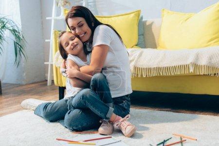 Glückliche Mutter mit geschlossenen Augen, die Tochter umarmt, während sie zu Hause auf dem Boden sitzt